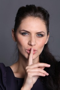 woman with a finger on her lips showing to keep silence